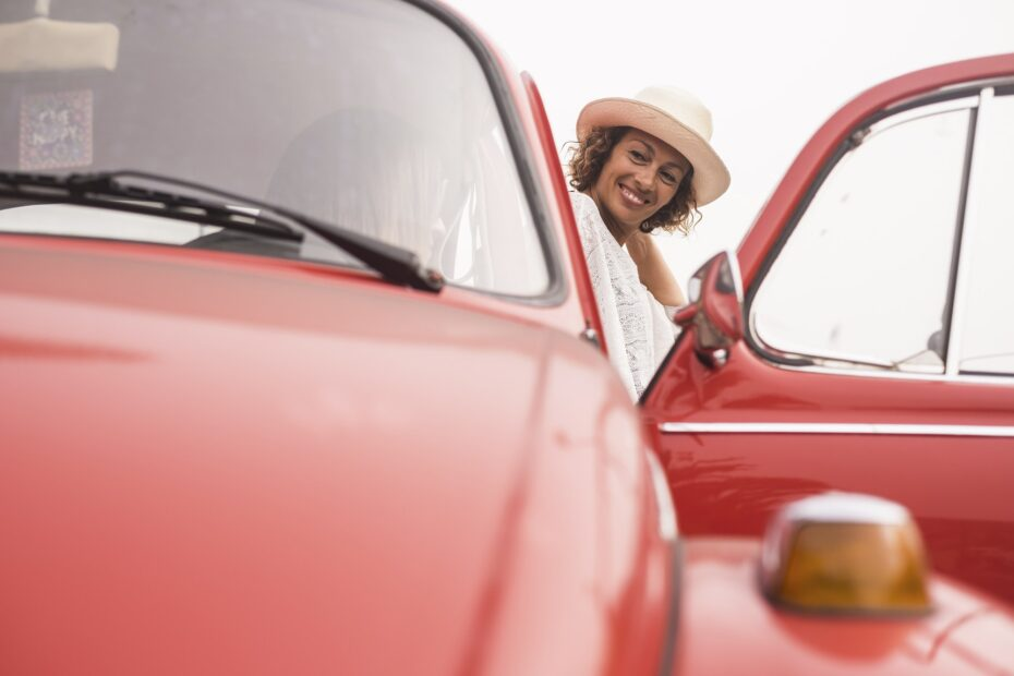 couple of women friends enjoying leisure activity with a red vintage retro car